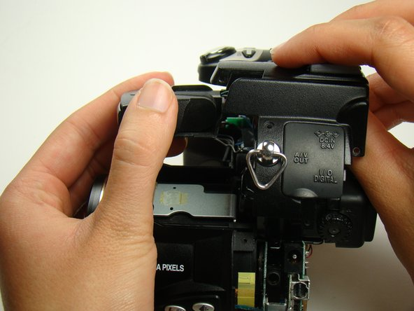 Image 2/2: Note: The top panel will be difficult to separate from the flash bulb housing. Place your hands as shown in the picture and push upward with your thumb while holding the flash bulb housing stationary