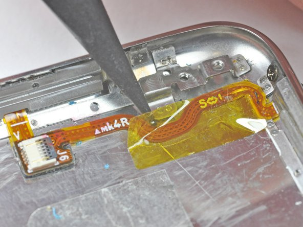 Image 1/1: Use the tip of a spudger to remove the yellow kapton tape covering the power/volume control ribbon cable.
