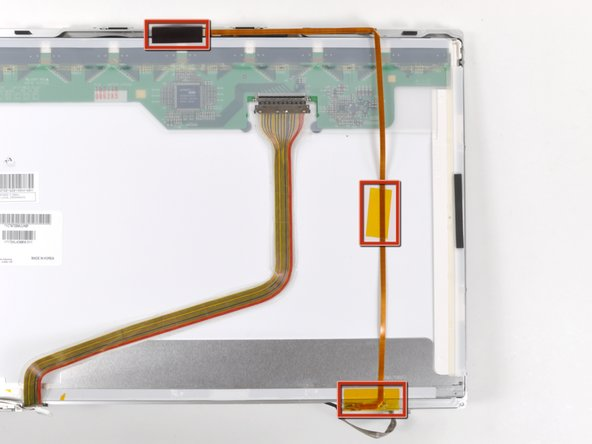 Remove the three pieces of tape securing the camera cable to the display assembly.