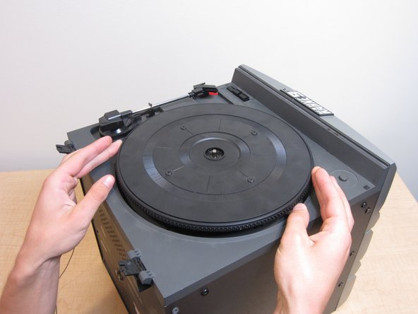 Separate the turntable from the top of the record player by lifting straight up.