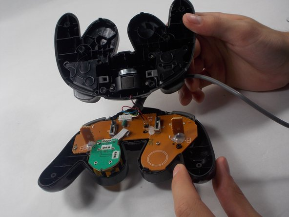 After separation, locate the rumble motor that is attached to the bottom cover of the controller.