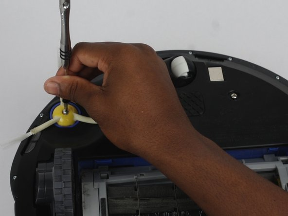 Flip the Roomba over and unscrew the side brush screw using the Phillips #2 screwdriver.