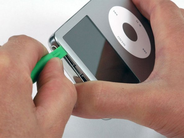Image 1/1: Near the other top corner, insert a plastic opening tool into the seam between the front and back of the iPod