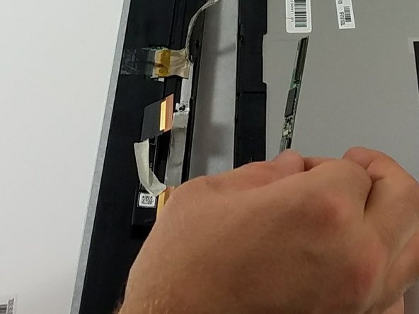 Pull the silicon strip away from the ribbon cables to disconnect it