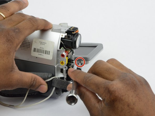 There is a 2.7 mm screw located where the  LCD monitor is connected to the main body of the camcorder. Remove the 2.7 mm screw.