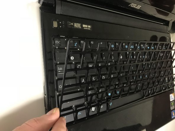 Use the plastic opening tool to pry open the keyboard cover.