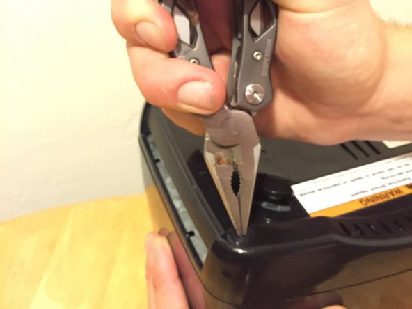 Use needle nose pliers to remove the rubber screw covers located on the four corners of the bottom of the toaster.