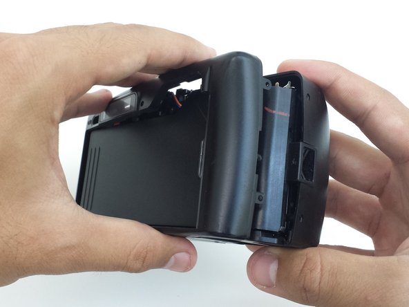 To remove back cover, begin by loosening the back cover from both the left and the right sides of the camera.