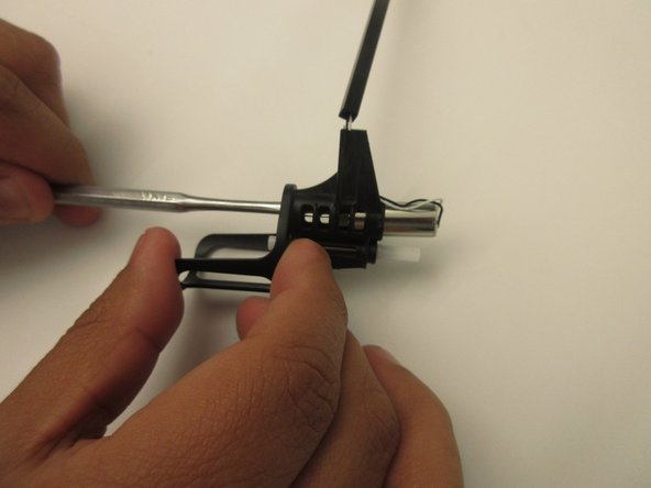 Use the thinner side of the spudger to push the motor through and out of the case.