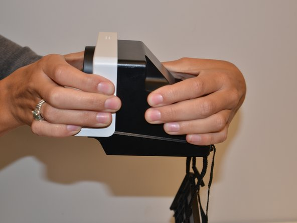 With force separate the front white piece from the back of the camera. You will use your hands to pull it apart.