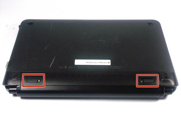 With the bottom of the HP Mini facing up, slide both switches inward towards each other.