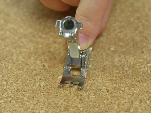Image 1/3: Take the foot at an angle and slide the hole in the top of the presser foot onto the peg on the sewing machine.