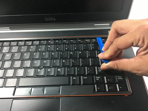 Use the plastic opening tool to remove the bezel from around the keyboard.