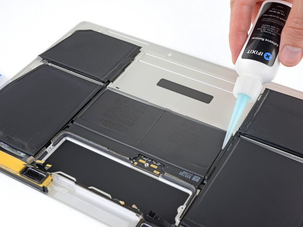 Lay the lower case assembly down flat, and apply adhesive remover to the two middle battery cells—at each side, and along the front edge (opposite the logic board area).