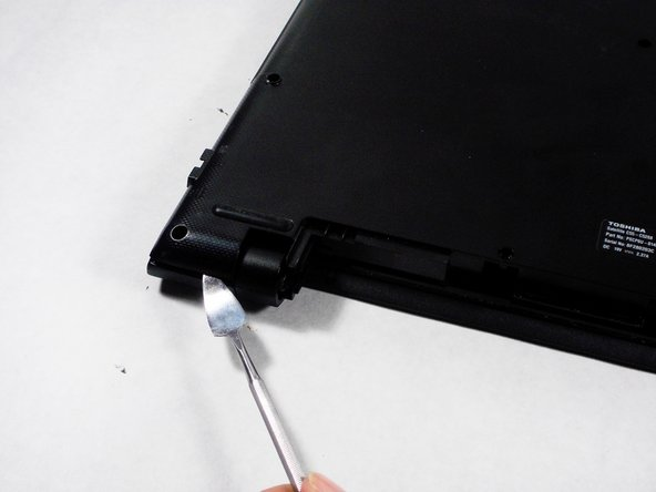 Image 1/2: Insert a metal spudger tool in the seam between the back cover and the laptop itself. Gently run the spudger around the edge to pop the cover off.