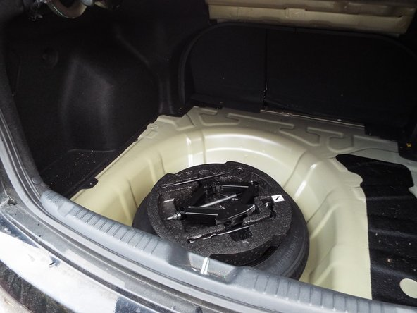 Spare tire and tools needed to change tire are located under the trunk mats.