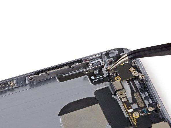 Pull the hold switch and volume control button brackets away from the rear case to allow access to the button covers.