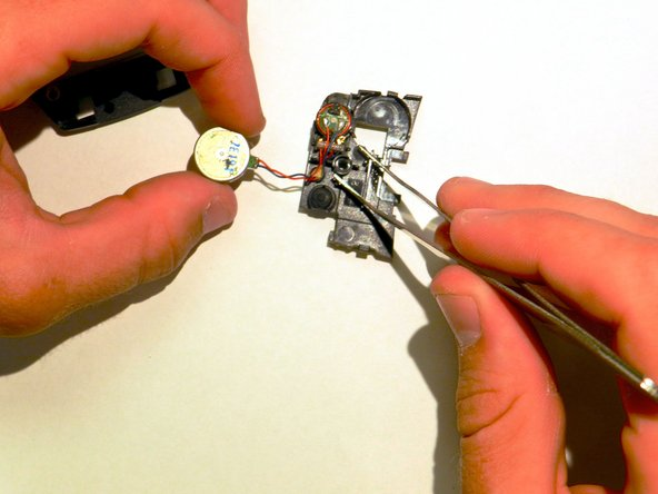 Use tweezers to remove the external speaker from the small unit.
