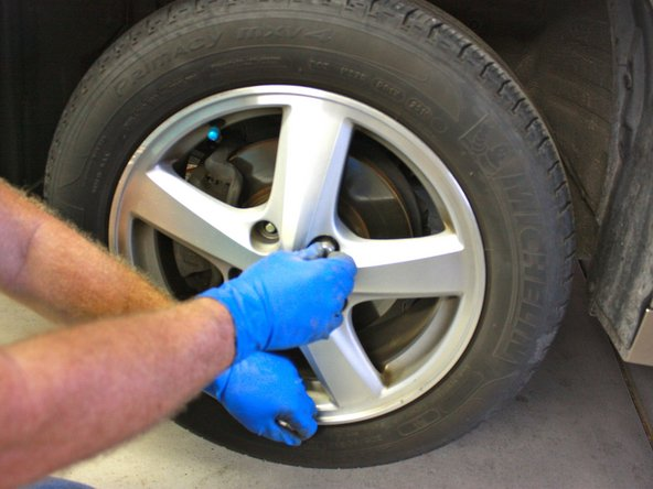 Remove the lug  nuts by loosening them with your hands.