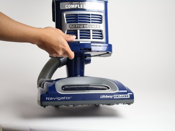 Lay the vacuum down by hand and locate the roller brush underneath the vacuum cleaner.