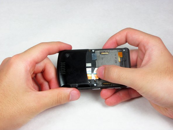 Remove the SIM card by pulling it toward the top of the phone with your thumb.