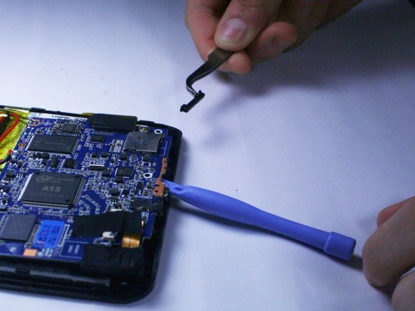 Image 2/2: Hold the circuit board up with the prying tool and extract the loose button with tweezers.