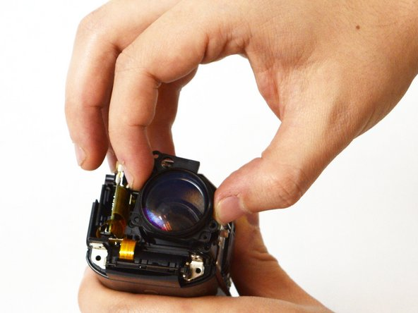 Grasp the plastic sides of the lens, and pull it away from the camera body to finish removing the lens.