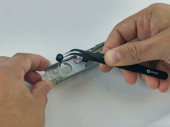 Using care to not damage the wires, remove microphone array from the retaining tabs on the plastic frame.