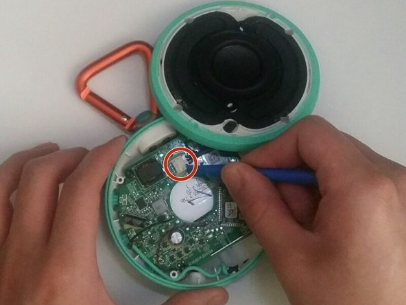 To completely remove the top portion, disconnect the speaker from the motherboard using the blue plastic opening tool.