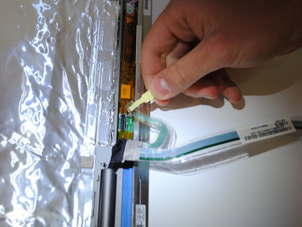Remove the cable at the base of the laptop by pulling up on the tab attached to the cable.