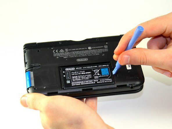 Insert the plastic opening tool into the opening located on the right side of the battery.