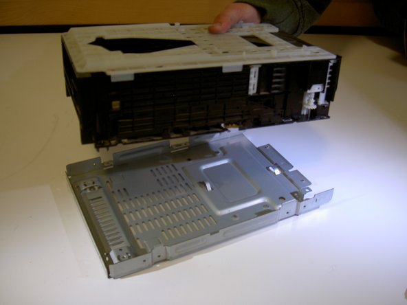 Lift the CD Tray Unit off of the bottom of the device and replace with new unit.