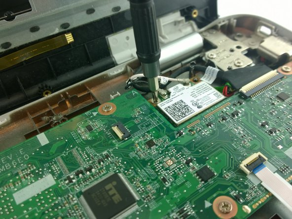 Remove the Phillips #0 4.5 mm screw from the wireless network card located in the back, right side of the interior.