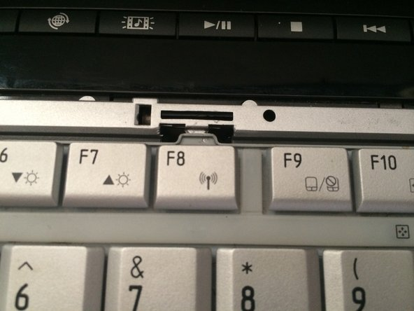 Use a plastic opening tool to press the key board's tab downward, until the key board is released.