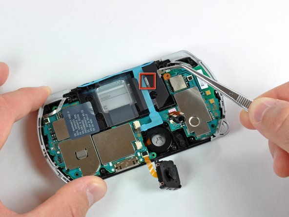 Image 1/1: Notice the little metal tab and slot (marked in red) where the clear plastic cover slides into. Make sure you slide the cover into place properly when reassembling the PSP Go.