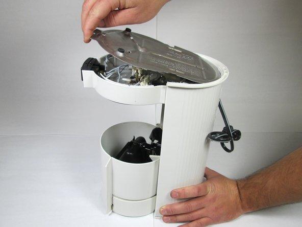 Hebe leicht den Bodendeckel ab und entferne ihn von der Maschine.