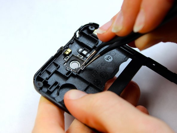 Using the precision tweezers, place the new camera lens into the lens cavity and align the clasps against the groves in the midframe.