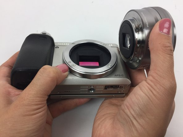 While holding the release button, twist the lens counterclockwise and pull it off.