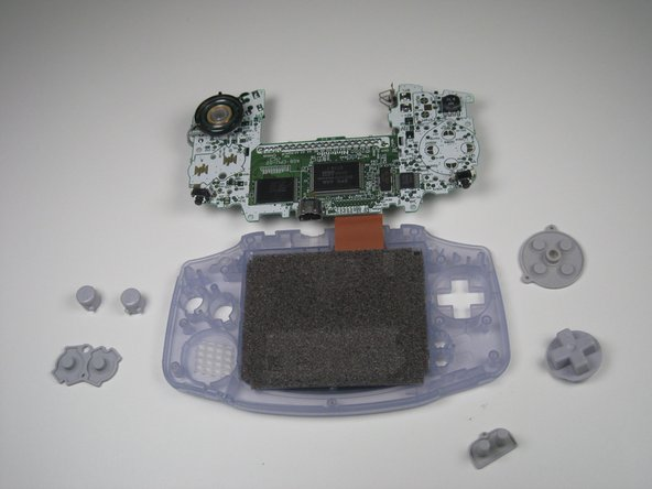 Image 3/3: Remove the plastic buttons and the D-pad from beneath the rubber pads with tweezers or by hand.