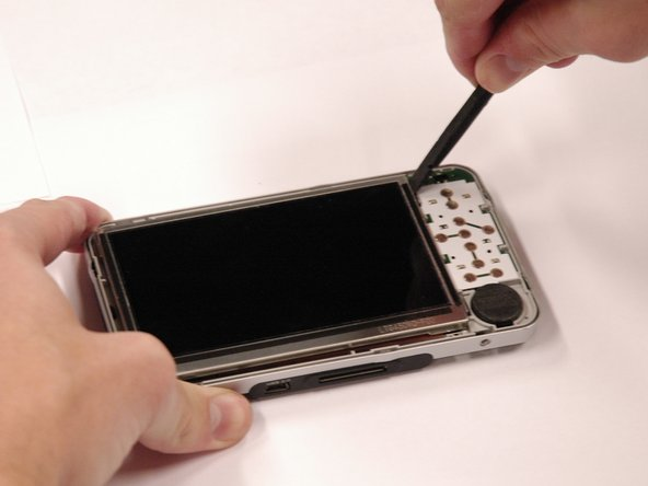 Use a spudger to separate the metal tabs that hold the screen in place on the right side.