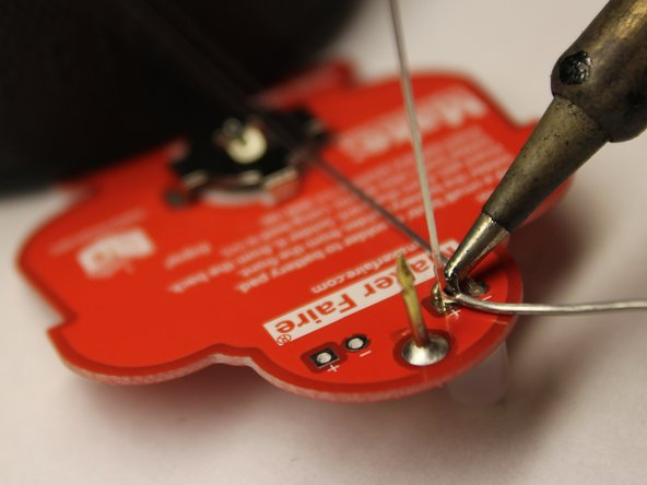 Begin heating up the junction between an LED lead and its pad by pressing the iron into the junction as illustrated.