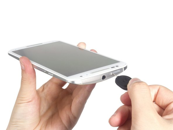Remove the SIM card tray by inserting the SIM card eject tool into the small hole on the tray.
