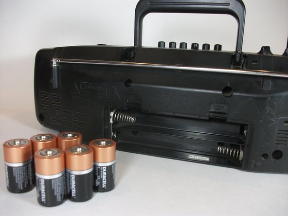 To insert the new batteries, push the negative end of the 1st battery against a spring and follow the diagram pictured to insert the batteries in the correct orientation.