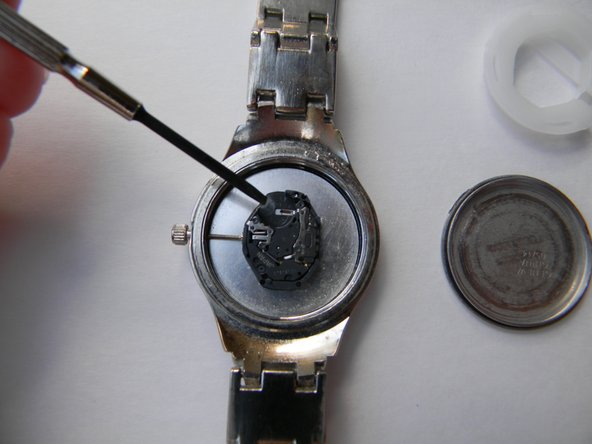 Take the old battery out of the watch. You can use the mini flat head screwdriver to do this.