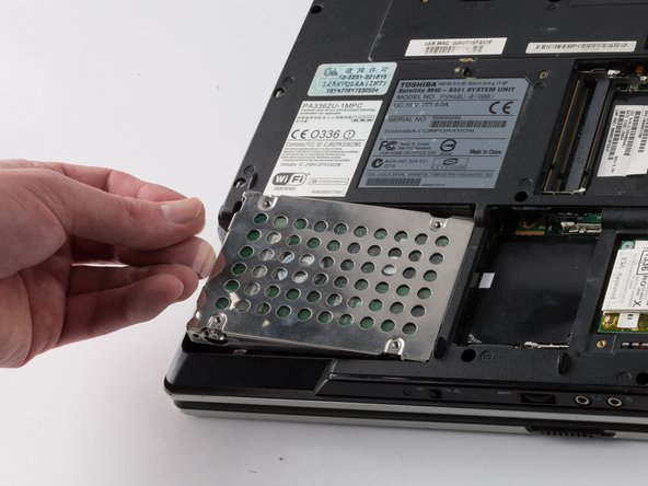 Use the plastic flap to pull the hard drive out of its slot.