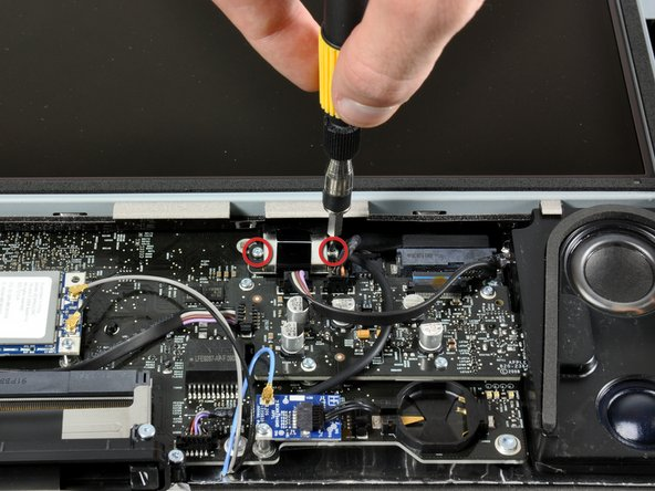 Image 1/2: Unscrewing the two T6 screws securing the display data cable.