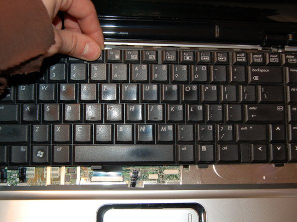 Lift up the back of the keyboard and slide it slowly towards the screen.  Unclip the ribbon cable near the touchpad.  Set the keyboard aside.