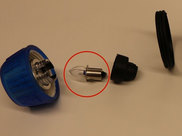 Image 2/3: The metal connector (red circle) easily slides out open end when twisting off the black socket. This metal piece connects the metal switch supplying power to the bulb.