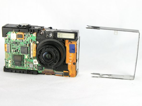 Remove the metal frame from the camera side closest to the flash, exposing the screw securing the flash assembly.