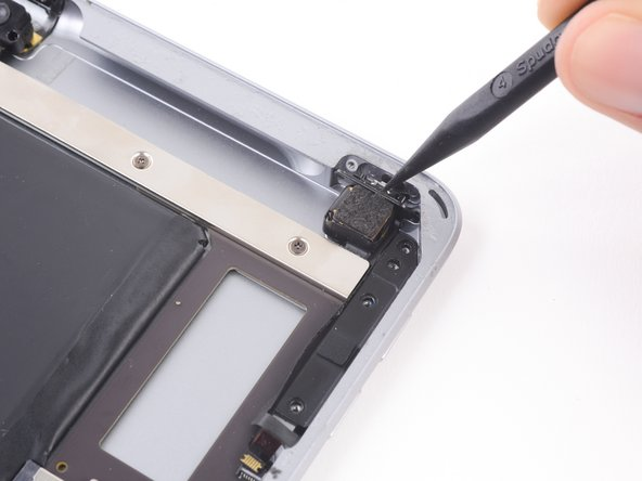 At this point, the volume button bracket may lift out of its slot. Do not remove it entirely as the ribbon cable is still glued to the rear case.